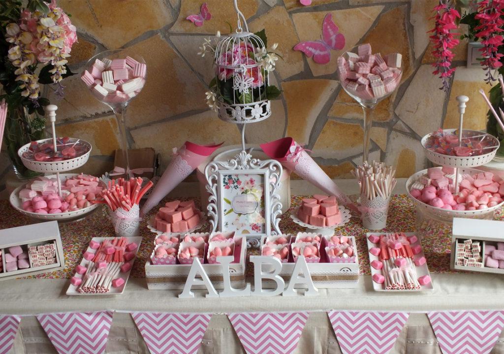 Cumpleaños de Alba en un entorno rural con tonos blanco y rosa con banderolas y dulces con el rosa predominante