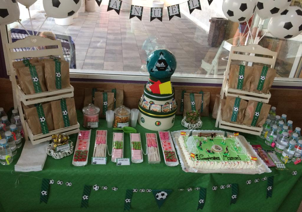 Para el cumpleaños de Manuel montamos la mesa dulce con tonos futbolísticos, tonos verde cesped, globos con forma de balón de fútbol, bolsas sorpresa para los invitados y distintos dulces.