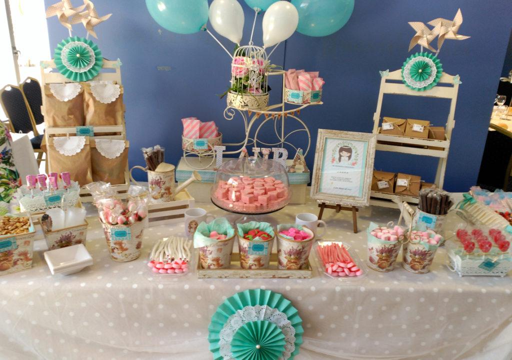 Para la comunión de Laura montamos esta elegante mesa dulce donde elegimos unos tonosaguamarina, blanco y tonos rosados, con piruletas, nubes, corazones, fresas y unos regalos sorpresa para los invitados.